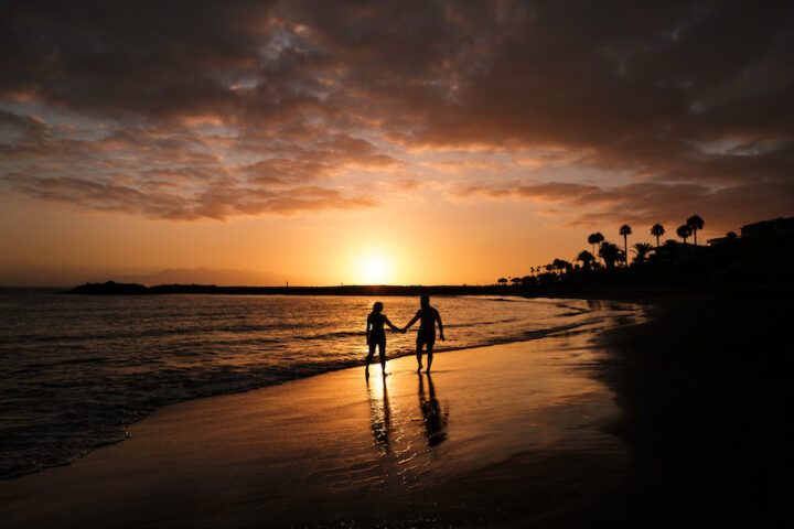 Romantic couple on the beach in a colorful sunset in the background.A guy and a girl at sunset on the island of Tenerife.