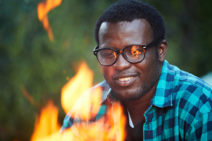 Young man in eyeglases and shirt looking at campfire during backpack trip at leisure
