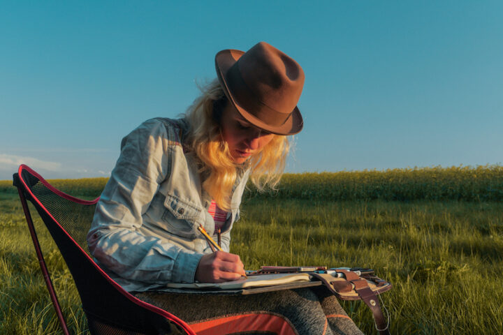 young caucasian female  artist sitting outdoors on a meadow and drawing a picutre into her notebook