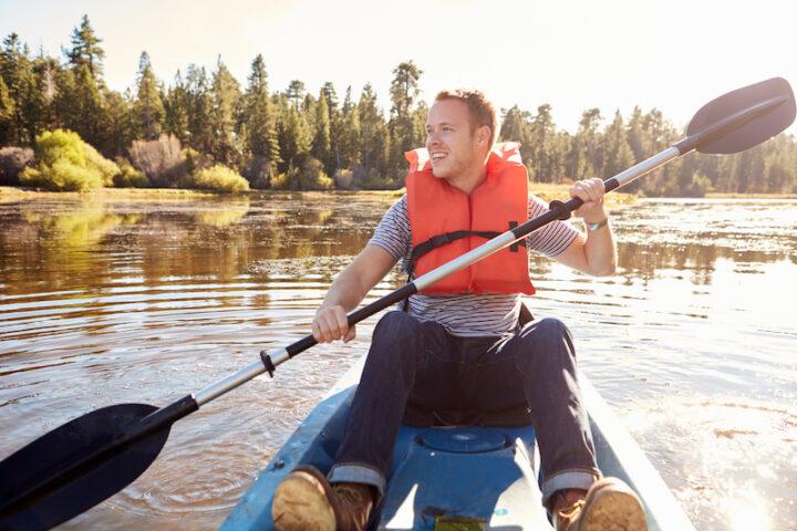 Man Wearing Life Preserver Rowing Kayak On Lake