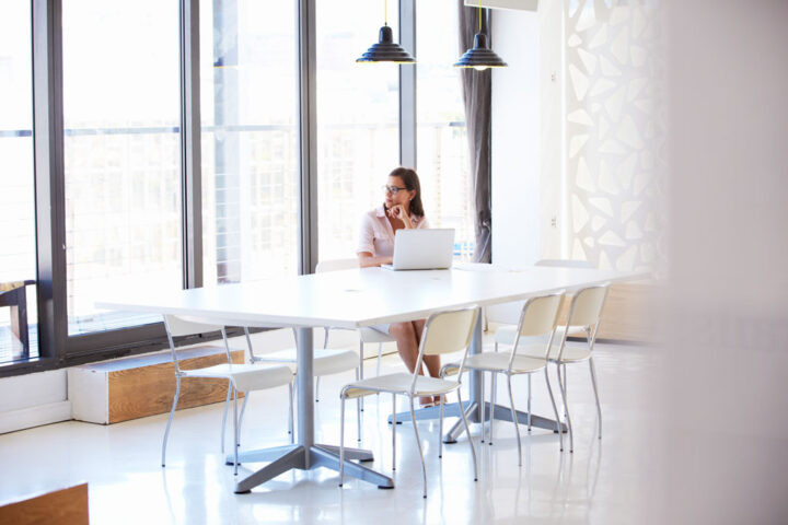 Young woman in empty meeting meeting room with large windows and white table