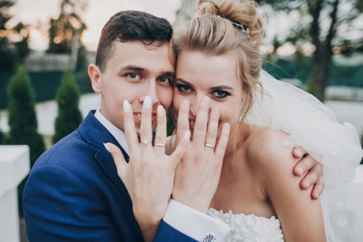 Stylish happy bride and groom showing hands with wedding rings at wedding reception outdoors