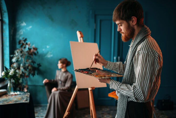 Male painter with palette and brush in hand paints woman's portrait on easel