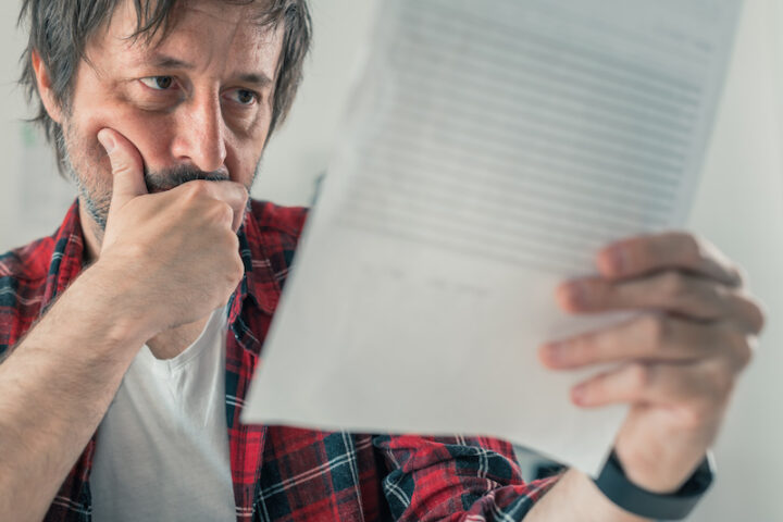 Worried freelancer reading business contract and terms of service document papers in home office, selective focus