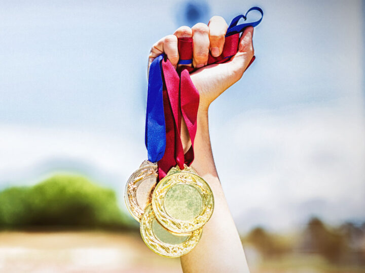 Hand of female athlete holding gold medal in stadium
