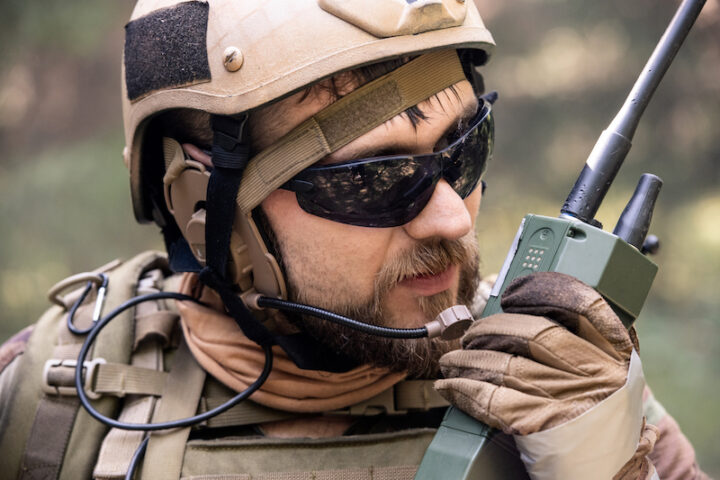 Close-up of bearded soldier in helmet and sunglasses using radio while taking message to colleague during military operation