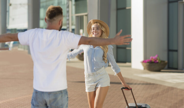 Back view portrait of man greeting woman with open arms after parting