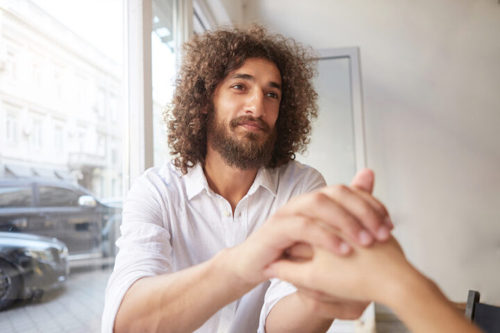 Young attractive curly man with beard and brown kind eyes sitting by the window, holding female hand and looking at her dearly, wearing white shirt