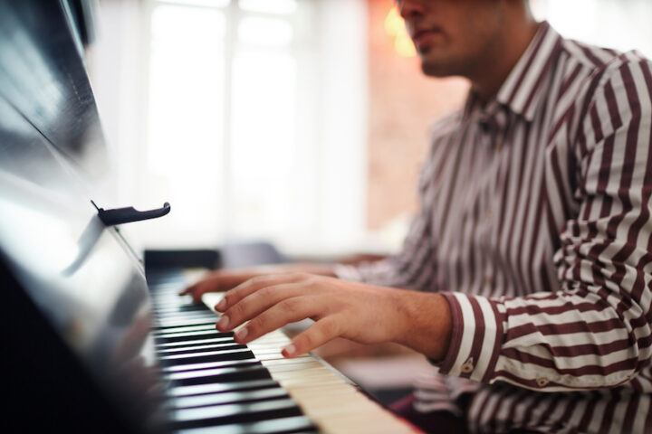 man with his hands over piano keys during play
