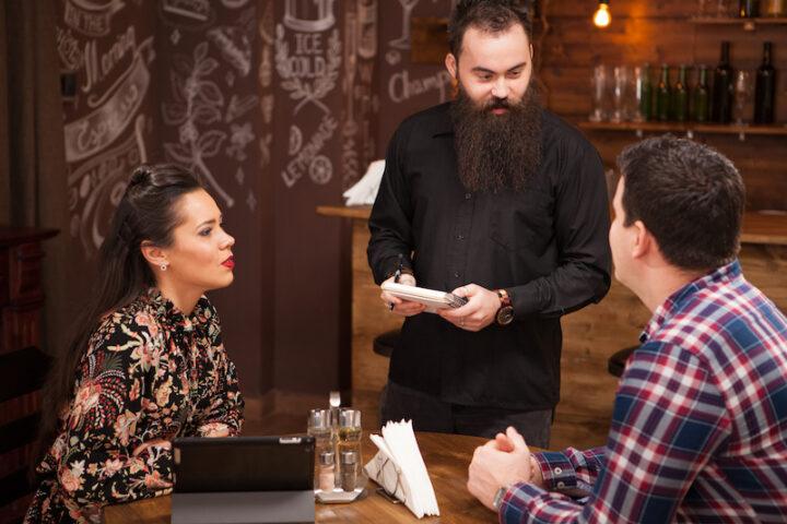 Waiter taking order from stylish couple in restaurant Hipster restaurant.