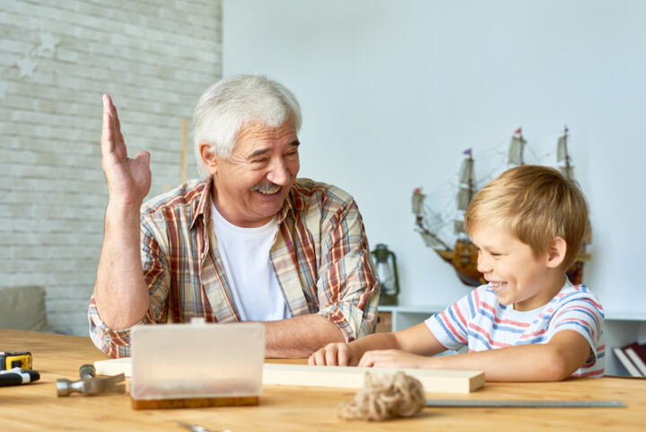 Portrait of happy senior man spending time with his grandson laughing together while teaching him woodwork