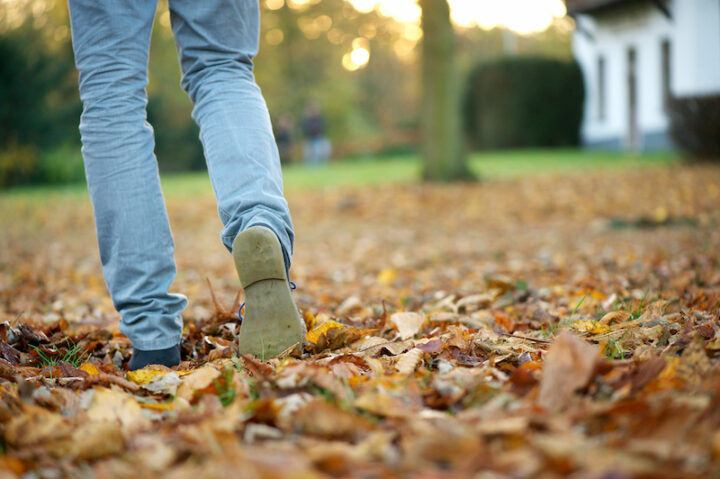Walking away in boots on brown autumn leaves