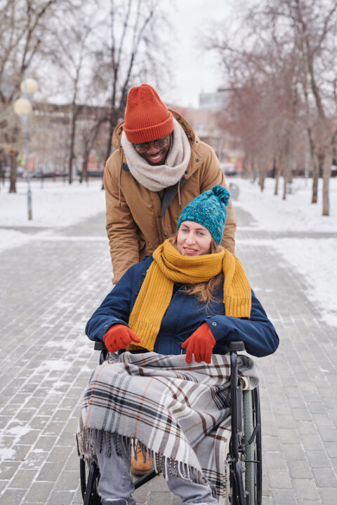 Young disabled white woman in wheelchair enjoying her walking on fresh air with black man behind her