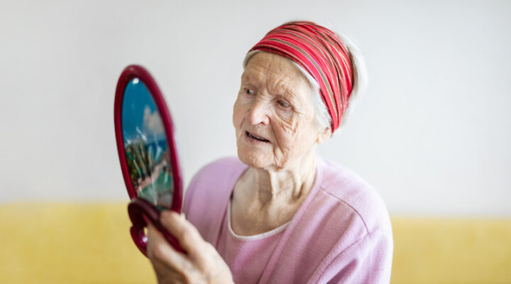 Caucasiasn senior woman looking at herself in mirror