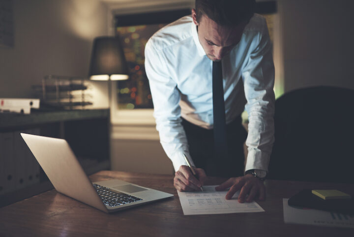 Lawyer signing document at night at office, working overtime