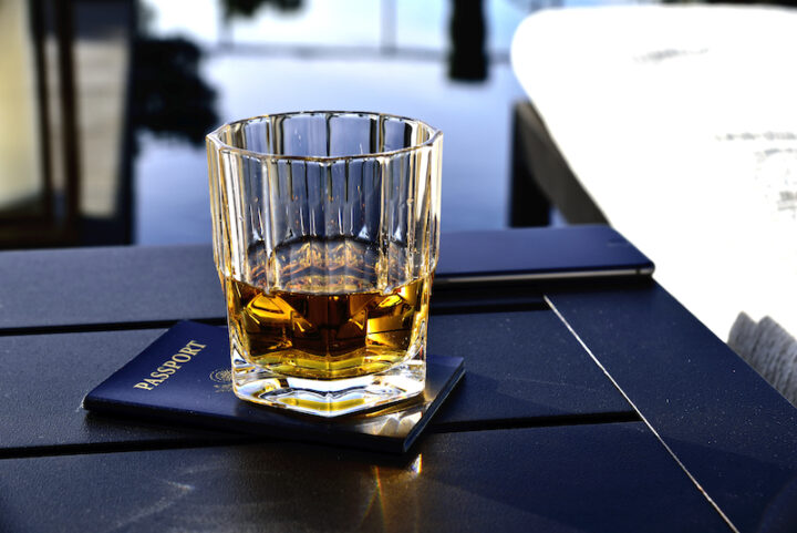 Glass of whiskey sitting on a passport