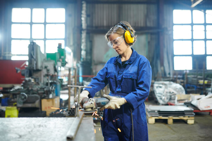 Portrait of modern female worker cutting metal at industrial plant or garage