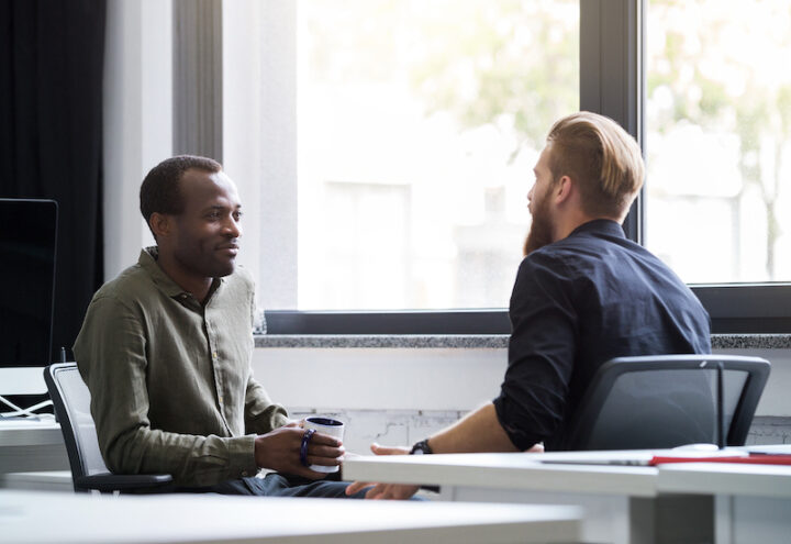 Two young male colleagues speaking to each other while sitting in an office