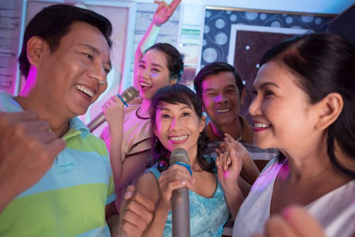 Senior Vietnamese woman singing in karaoke with her friends