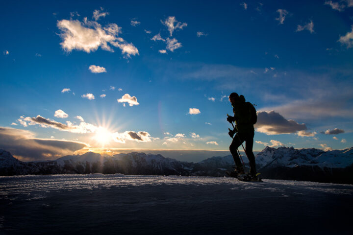 man hiking at the top of the a mountain in winter season.