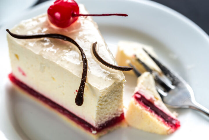 piece of raspberry cheesecake with sweet cherry on top