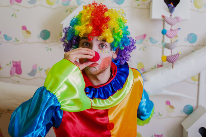 Funny clown with colorful hairstyle pushes himself on the red nose