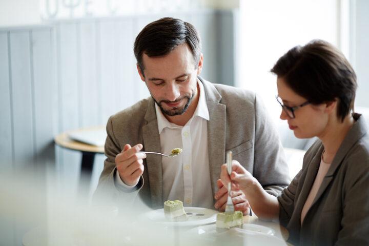 Modern business employees having tasty dessert in cafe
