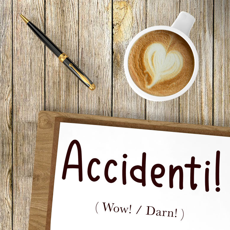 """cover image with the word """"accidenti"""" and its translation written on a notepad next to a cup of cofee"""