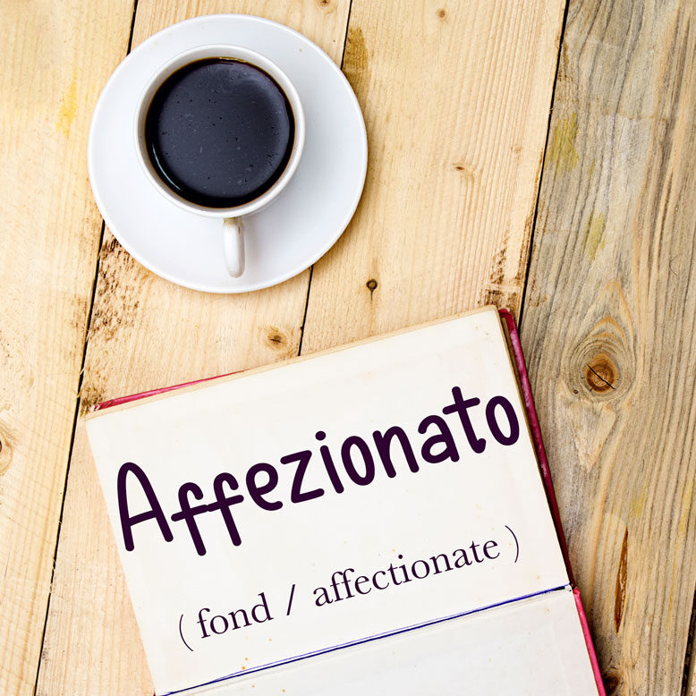 """cover image with the word """"affezionato"""" and its translation written on a notepad next to a cup of cofee"""
