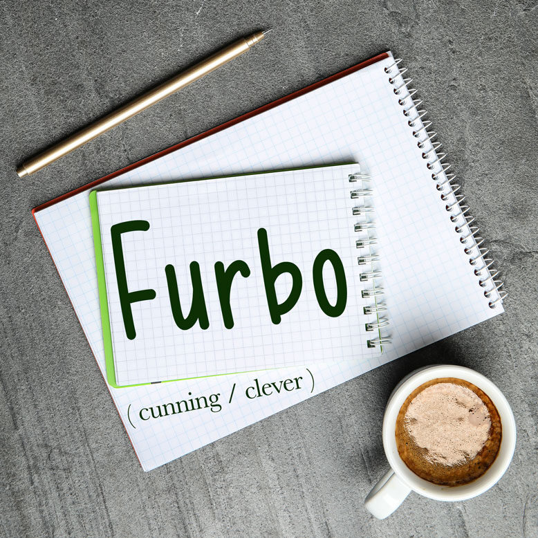 """cover image with the word """"furbo"""" and its translation written on a notepad next to a cup of cofee"""