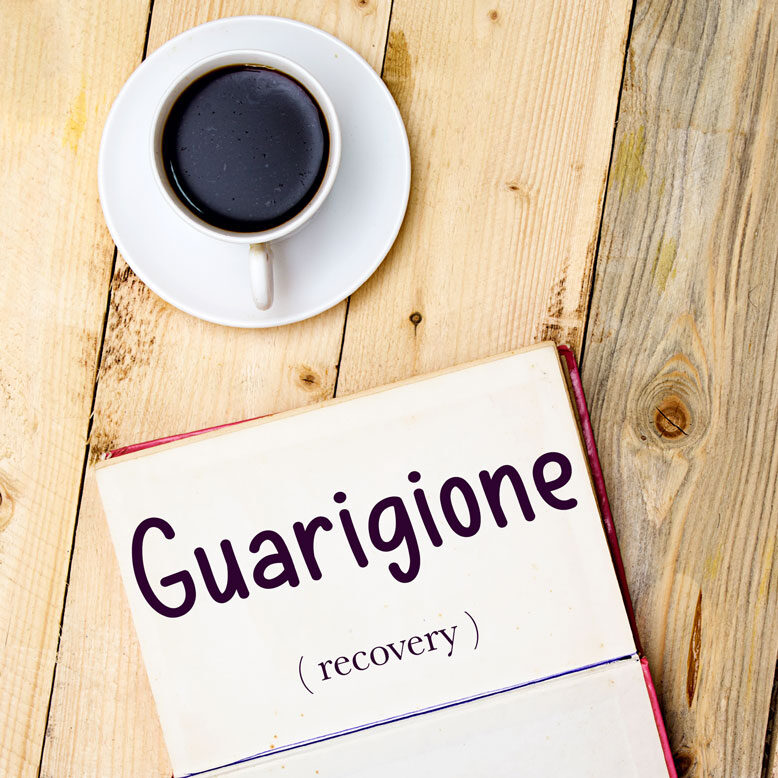 """cover image with the word """"guarigione"""" and its translation written on a notepad next to a cup of cofee"""