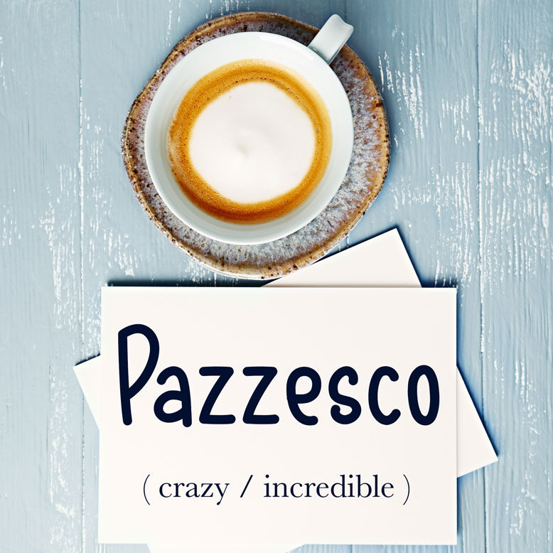 """cover image with the word """" pazzesco"""" and its translation written on a notepad next to a cup of cofee"""