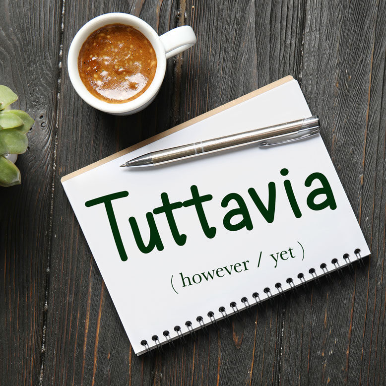 """cover image with the word """"tuttavia"""" and its translation written on a notepad next to a cup of cofee"""