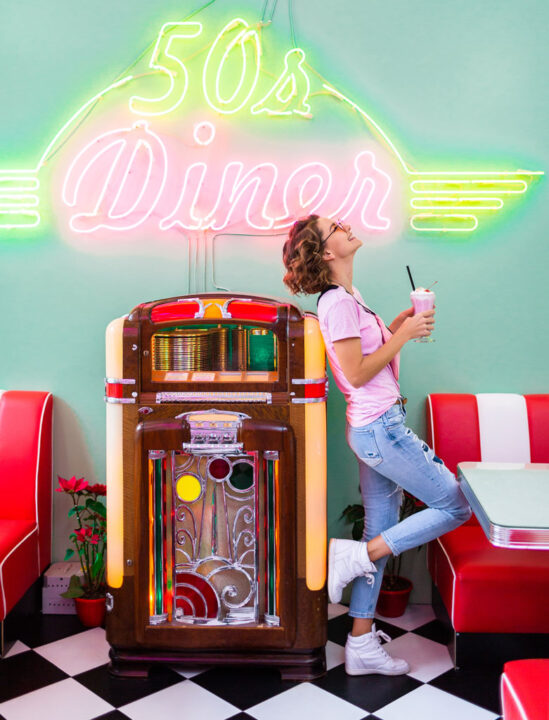 stylish attractive smiling woman in retro vintage 50's cafe at music jukebox drinking milk shake cocktail in hipster outfit having fun laughing in cheerful mood