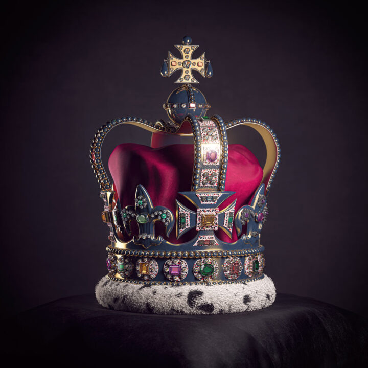 Royal golden crown with jewels on pillow on black background