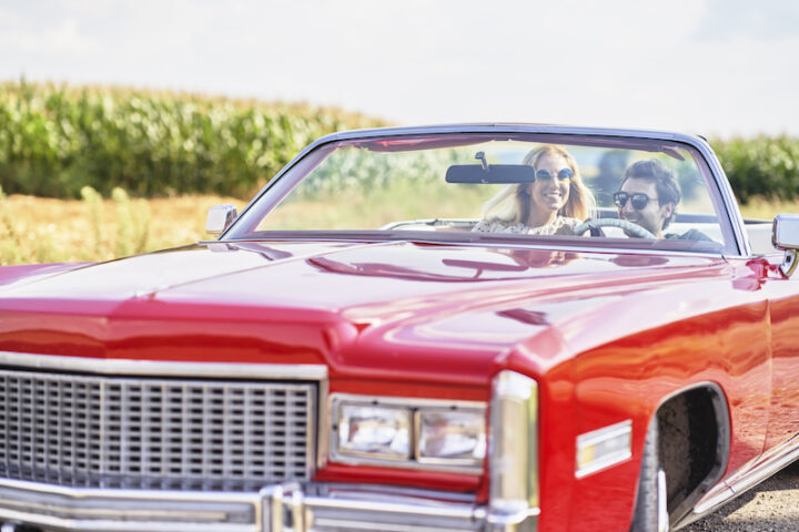 Smiling couple in a red old car