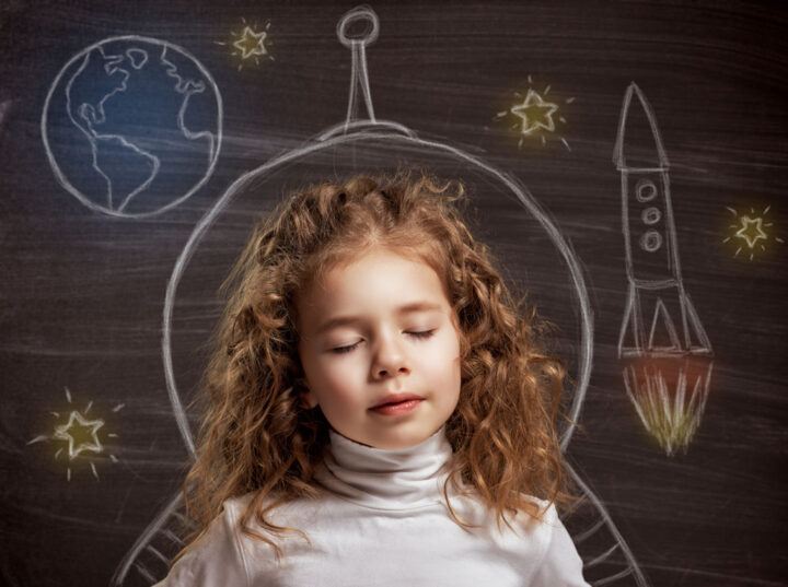 child dreaming with the earth, a rocket and a space ship drawn on a blackboard in the background