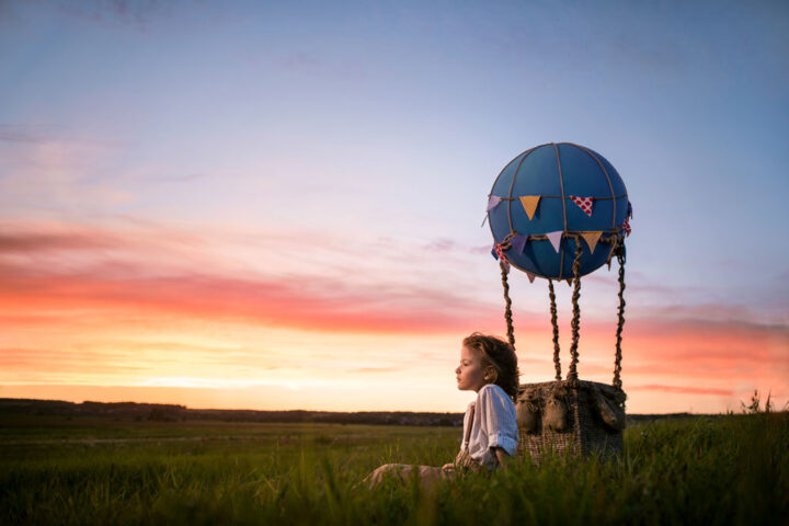 Little boy with aerostat in the field at sunset