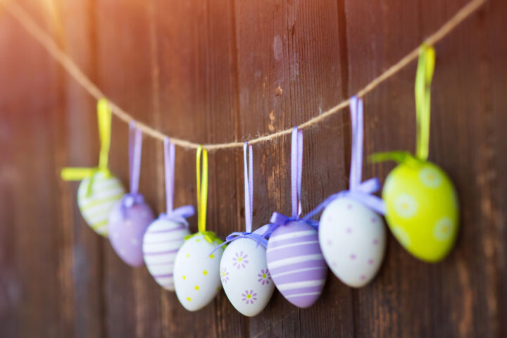 Colorful easter eggs hanging on a twine at the wooden wall background.