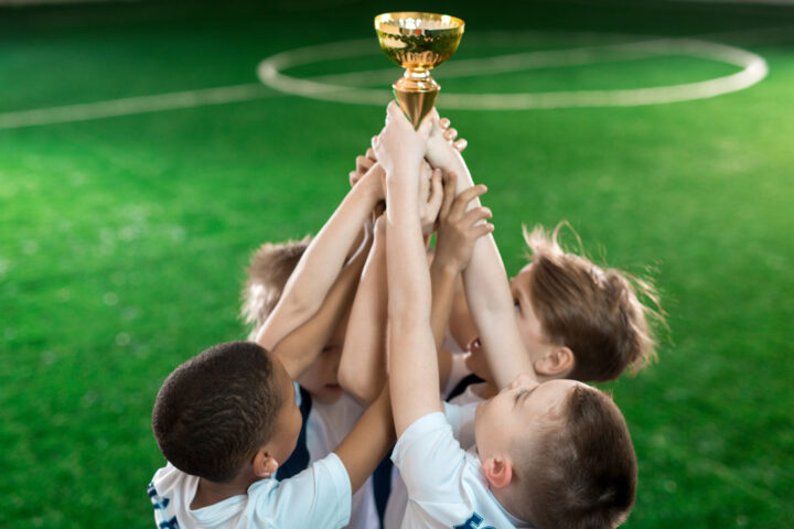 Group of young football champions raising hands with gold award
