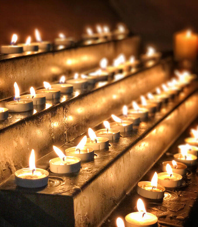 Rows of prayer candles glow brightly in a cathedral