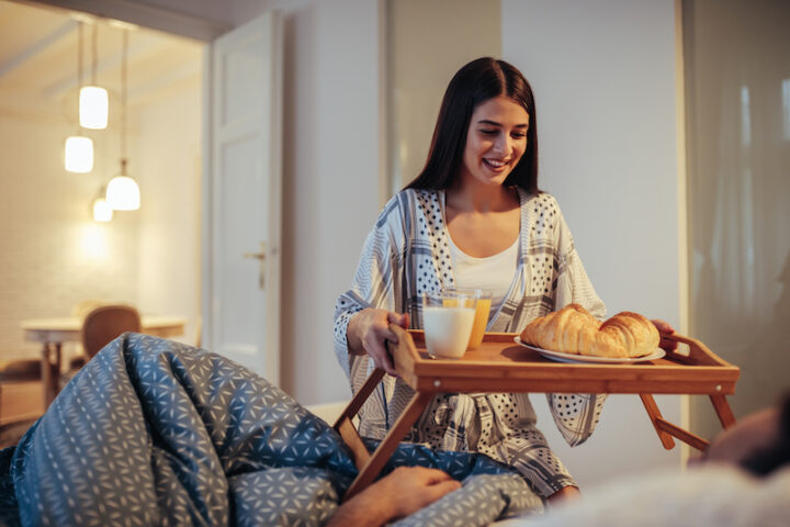 Girl bringing food to her boyfriend in bed.