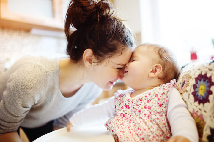 Young mother and her little daughter having breakfast together