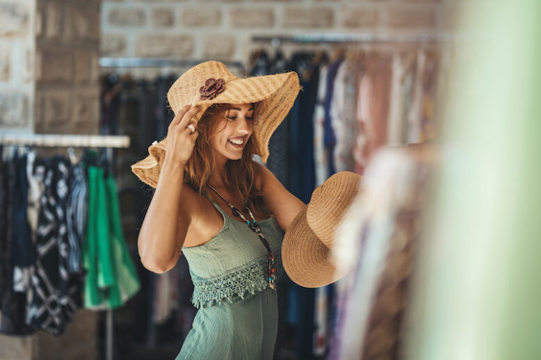 A beautiful smiling young woman is walking along the streets of a Mediterranean town and enjoys in summer sunny day.  She chooses a new hat, wanting to buy it.