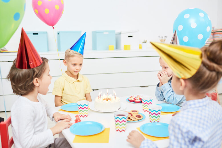 Group of little kids sitting around served festive table and going to have deserts with drinks