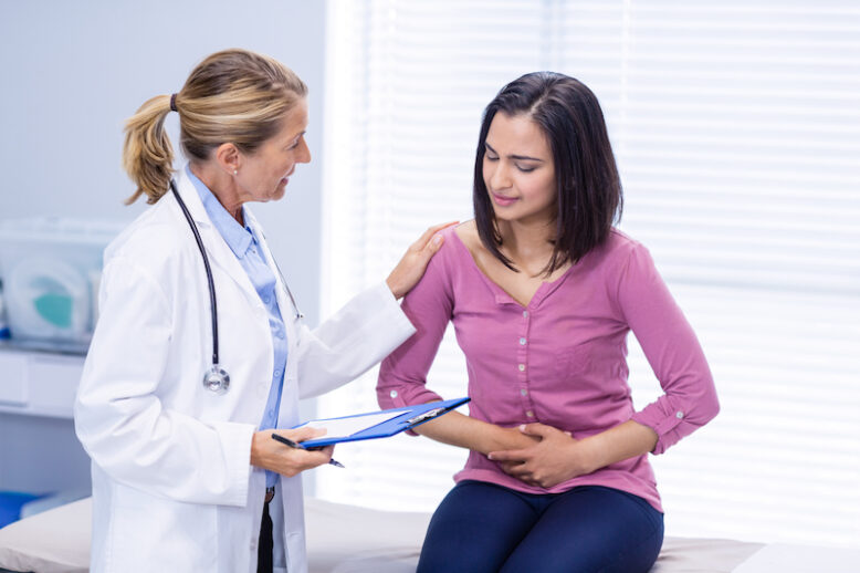 Patient suffering from stomach ache while consulting doctor in clinic