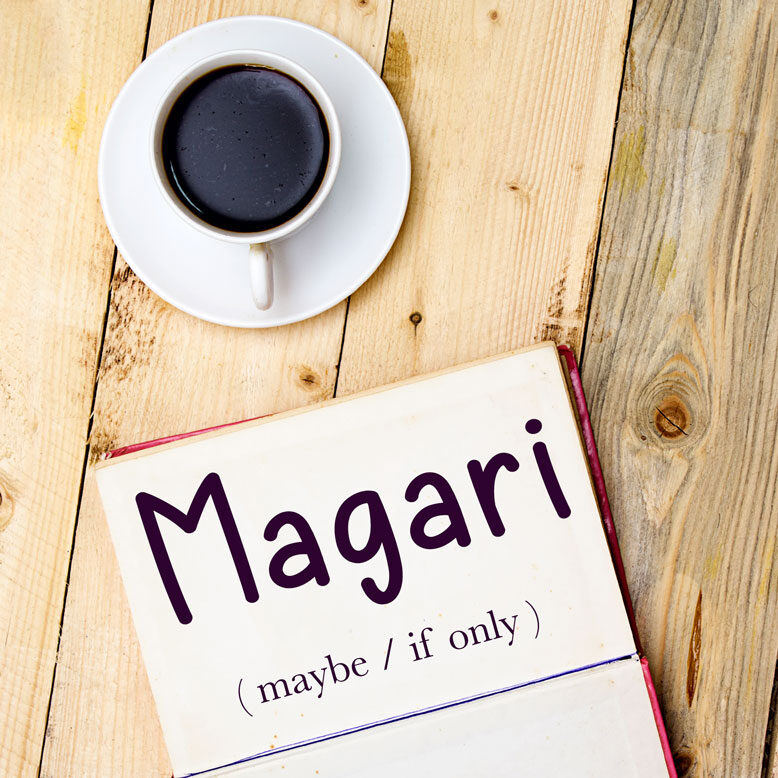 """cover image with the word """"magari"""" and its translation written on a notepad next to a cup of cofee"""