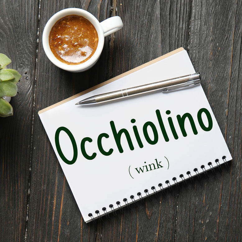 """cover image with the word """"occhiolino"""" and its translation written on a notepad next to a cup of cofee"""