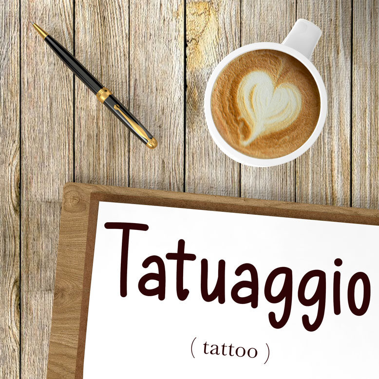 """cover image with the word """"tatuaggio"""" and its translation written on a notepad next to a cup of cofee"""