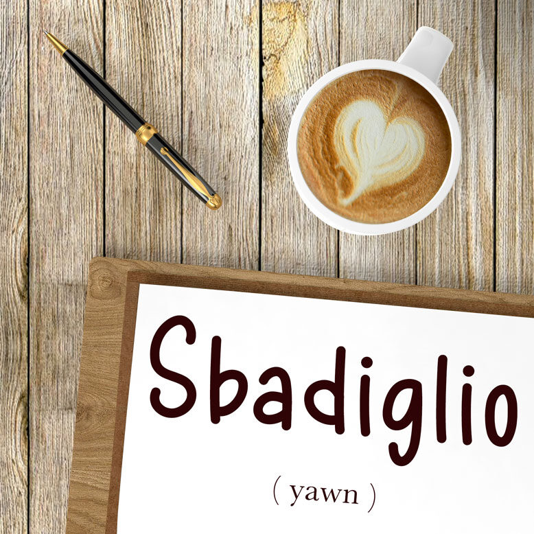 """cover image with the word """"sbadiglio"""" and its translation written on a notepad next to a cup of cofee"""